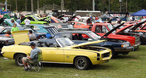 Car show with a bright yellow car in forefront