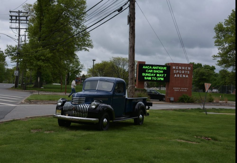 Antique black pickup parked on grass in front of LED sign
