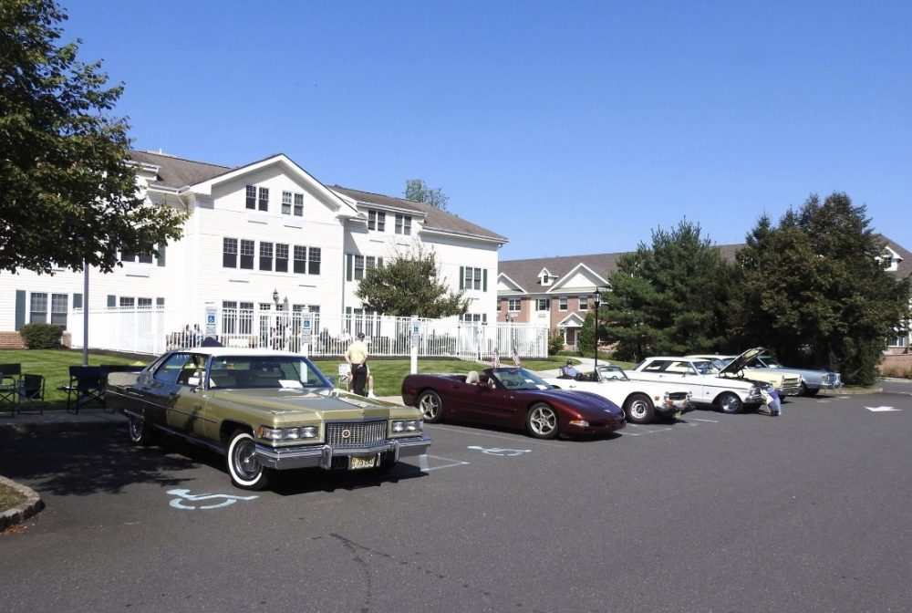Several vintage cars parked in front of a care facility